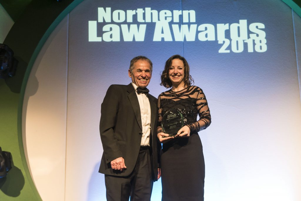 Dr Tyrrell smiling and receiving Law Teacher of the Year Award